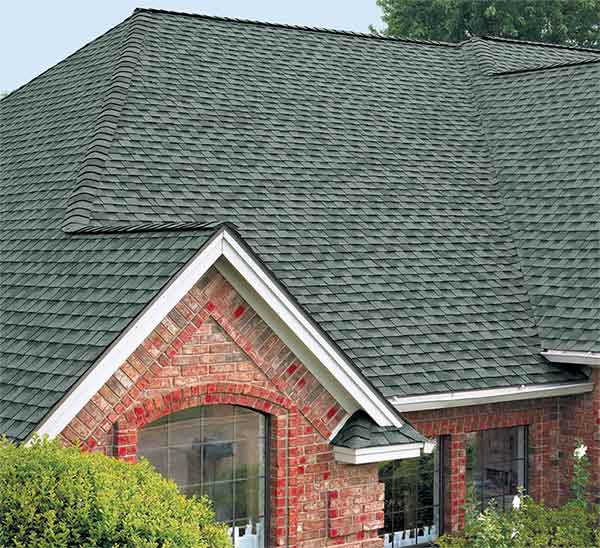 Green high definition shingles against a red house - pretty
